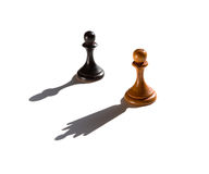 Two chess pawns one casting a queen piece shadow. Concept of strength and aspirations stock photos