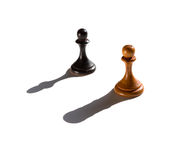 Two chess pawns one casting a rook piece shadow. Concept of strength and aspirations royalty free stock image