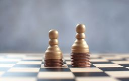 Wage gap chess concept. Two chess pawns with on top of a heap of coins stock photography