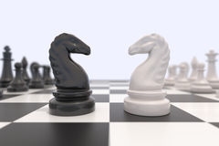 Two chess pieces on a chessboard. Black and white knights facing each other. Competition, discussion, agreement or opposition and confrontation concept Stock Images