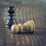 Two chess pieces on wooden table. Stock Images