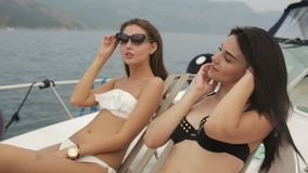 Two chic girls in bikinis lying on a yacht stock footage