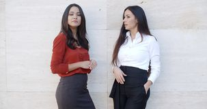 Two chic young women standing chatting. Two chic relaxed young women standing chatting together in front of a white exterior wall with bilateral copyspace  three stock video