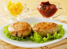 Two chicken cutlets on the green leaf lettuce. Royalty Free Stock Photography