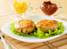 Two chicken cutlets on the green leaf lettuce. Decorated with fresh vegetables Royalty Free Stock Photography