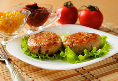 Two chicken cutlets on the green leaf lettuce Royalty Free Stock Images