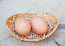 Two chicken eggs in bamboo basket Stock Photo