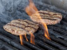 Two Chicken meat burger steaks on the grill with flames. cookin. G chicken grilling or bbq or barbecue on charcoals. Close up Royalty Free Stock Image