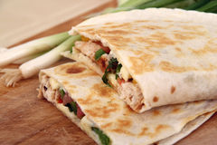 Two chicken quesadillas. On cutting board stock photo