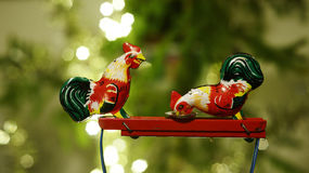 Two chickens peck grain from a plate, metal toy Stock Image