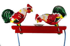 Two chickens peck grain from a plate, toy Stock Photo