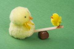 Two chicks on a see saw. Two cute yellow furry chick toys on a teeter totter.One is big and he is weighing down the small chick stuck at the top. Green Royalty Free Stock Photography