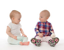 Two child baby girls toddlers sitting. And happy looking smiling at each other on a white background Stock Photo