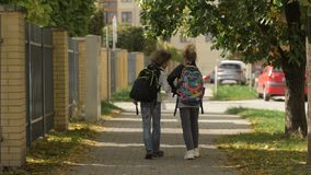 Two Child Girl and Boy Walking on city streets past cars. Sister with her Brother Back to School. Children carry stock video footage