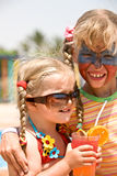 Two child girl with paint on face drink  juice. Stock Image