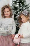Two child girls with gifts, Christmas tree Stock Photo