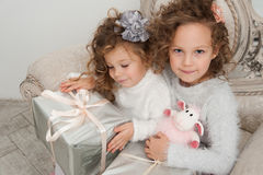Two child girls with gifts on coach at Christmas time Stock Images