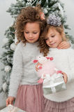 Two child girls with gifts and sheep toy near christmas tree Royalty Free Stock Photography