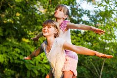 Two child girls playing together. Sisters play Superhero. Happy kids having fun, smiling and hugging. Family holiday and togetherness. Girl power concept royalty free stock image