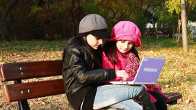 Two child girls sitting on bench and playing on laptop. Sisters have a fun time on laptop. Autumn stock video
