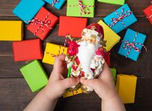 Two child hands hold Santa Claus toy with hope for presents Stock Photos