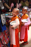 Two child nuns with alms bowls filled with rice, Burma. Two child nuns with alms bowls filled with rice collecting the offerings at the market in Myanmar/Burma Royalty Free Stock Image
