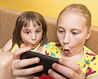 Two child play on your mobile phone. Royalty Free Stock Image