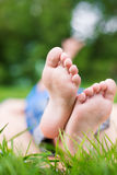 Two Child's crossed foots. Crossed foots of lying child on picnic or yoga. Selective focus stock photography