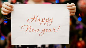 Two child`s hands hold a piece of paper with a congratulation happy new year stock video footage