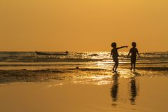 Two child shadows on the beach with gold light sunset Stock Images