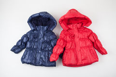 Two child warm jackets. Red and blue Royalty Free Stock Photos