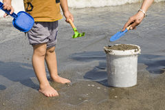 Two Child Working Together for Filling the Bucket at Sea Shore royalty free stock image