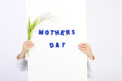 Two childhood hands holding white board with blue text Mothers day and one white and violet tulip Stock Photos