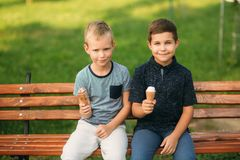 Two childre sitting on the bench and eating ice cream.  Stock Photo