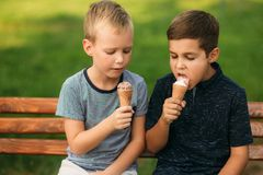 Two childre sitting on the bench and eating ice cream.  Royalty Free Stock Image
