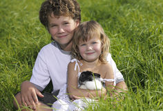 Two children. Smiling sitting on green grass with rabbit Royalty Free Stock Image