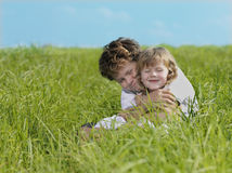 Two children. On green grass smiling Stock Image