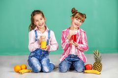 Two children argue for pineapple. Sisters in jeans. The concept. Of a healthy lifestyle, food, childhood, vitamins, vegetarianism Stock Photos
