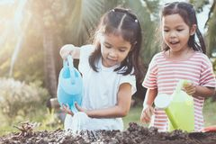 Two children asian little girl having fun to prepare soil. For planting seedling young tree together in vintage color tone Royalty Free Stock Image