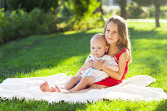 Two children baby brother and sister on green meadow Royalty Free Stock Photos