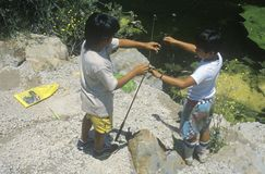 Two children baiting hooks and fishing, Malibu, CA Stock Photo