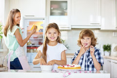 Two children baking and tasting a fruit cake Royalty Free Stock Images
