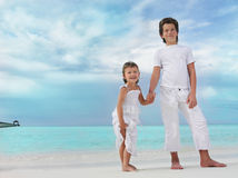 Two children on the beach. In white cloths Stock Image