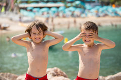 Two children on the beach, boys, playing and making funny faces Royalty Free Stock Photos