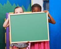 Two children behind empty chalkboard Royalty Free Stock Photo