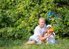 Two children blow bubbles Stock Photo