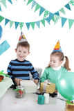 Two children at blue party table openning present Stock Photo