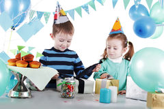 Two children at blue party table openning present Stock Photos