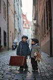 Two children, boy brothers, carrying suitcase and dog toy, travel in the city alone royalty free stock photo