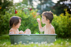 Two children, boy brothers, having a bath outdoors, making soap Stock Images